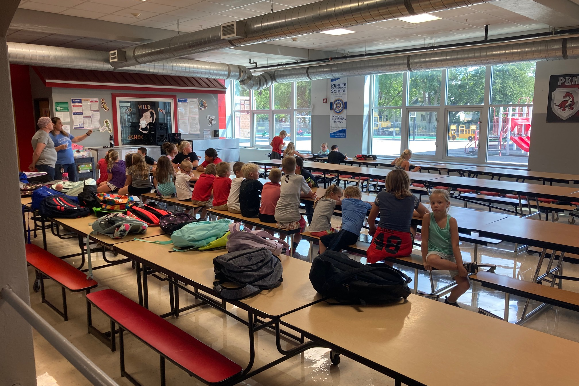 students sitting in the Pender cafeteria listening to their teachers