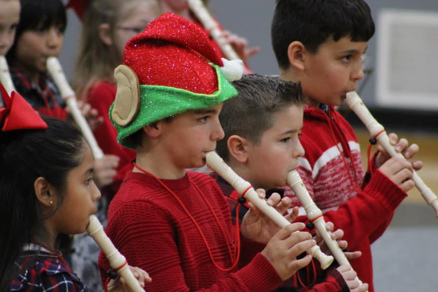 Student play recorders at Christmas concerts in holiday outfits