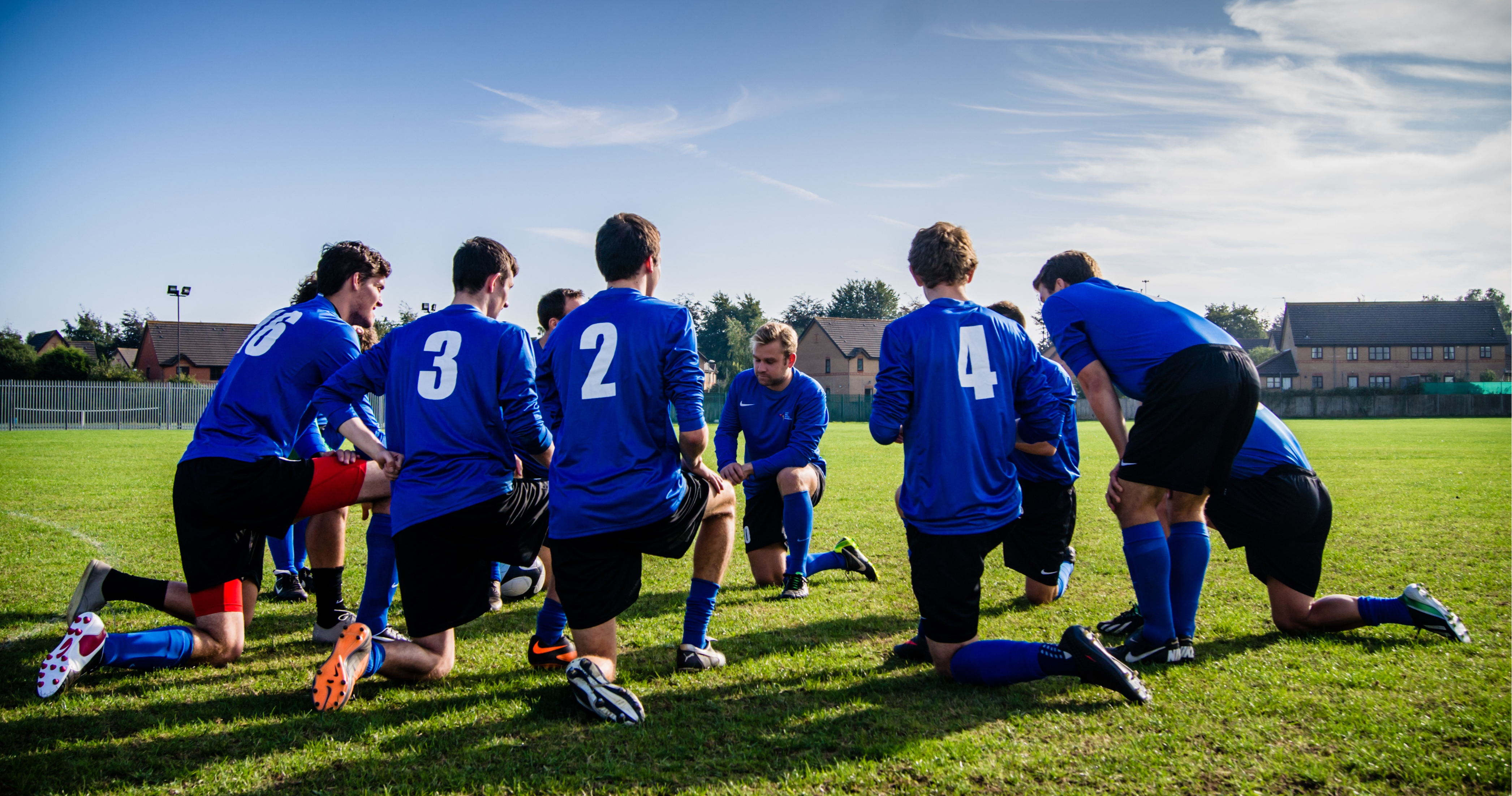 Soccer players kneel on a field.
