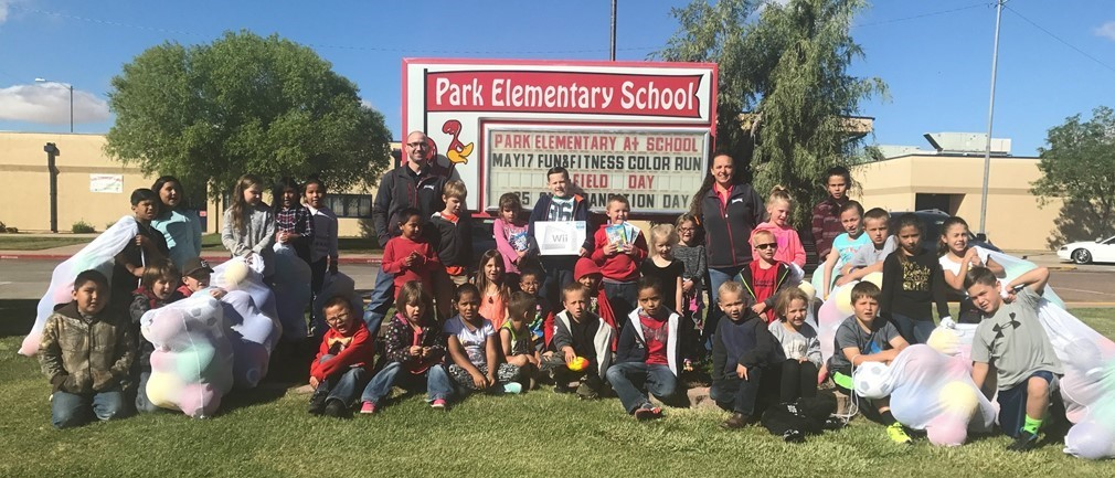 Staff and students pose by school sign
