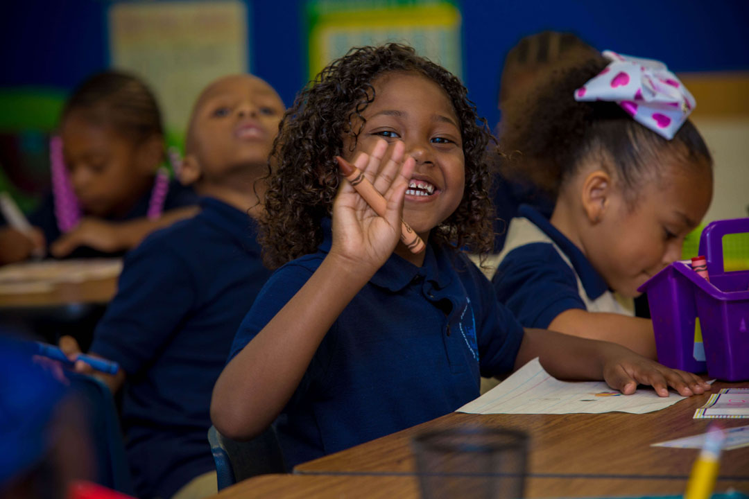 smiling student waving