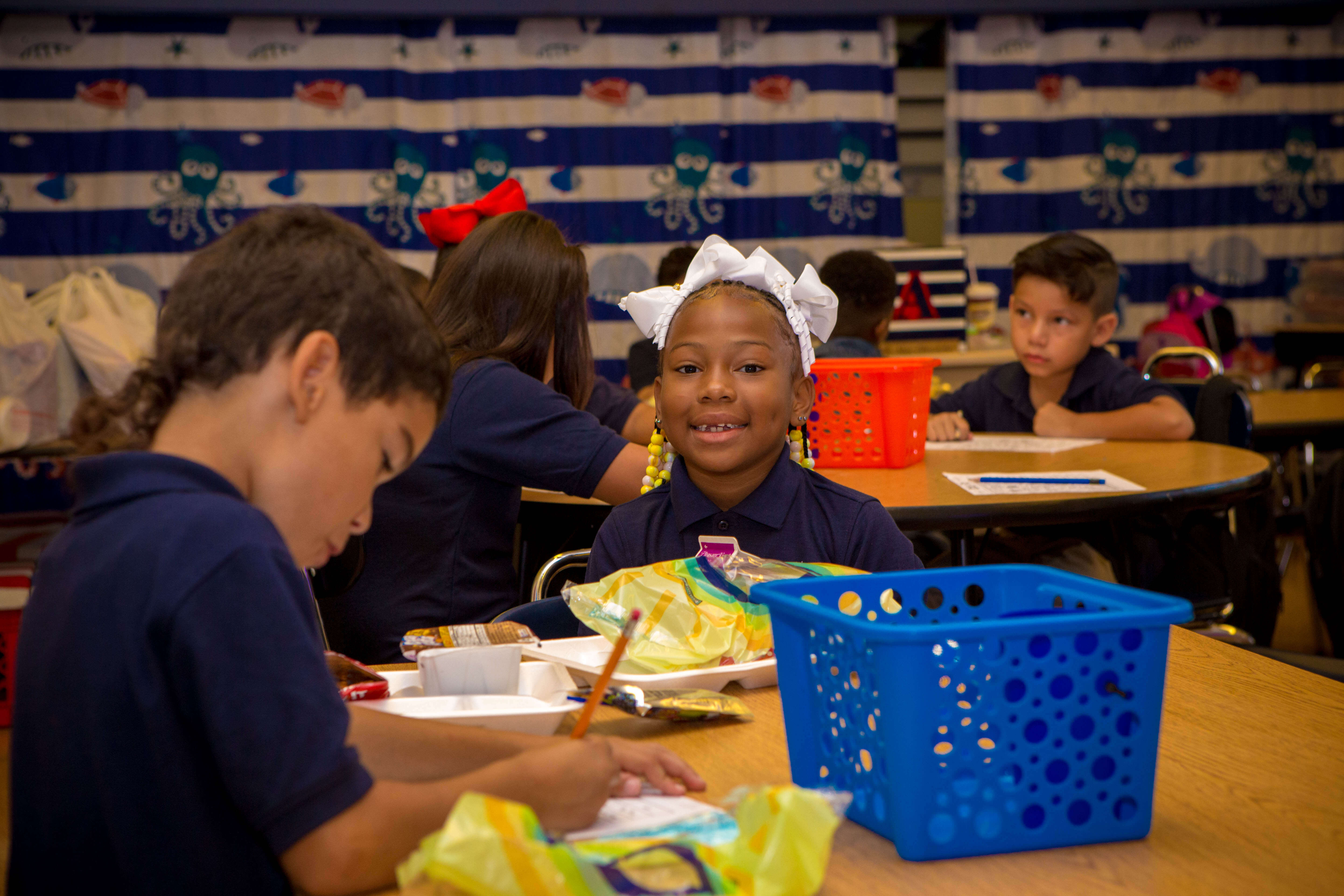 students with lunch trays in classroom