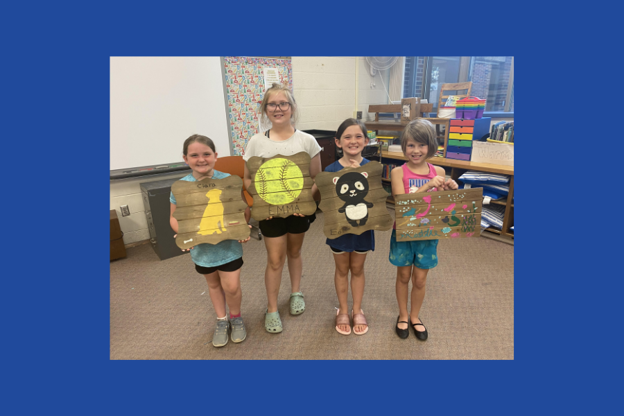 Four girls post with designs they've painted onto wooden boards