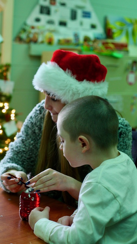 Older female student wearing a Santa Claus hat sitting with a younger student with a buzz cut