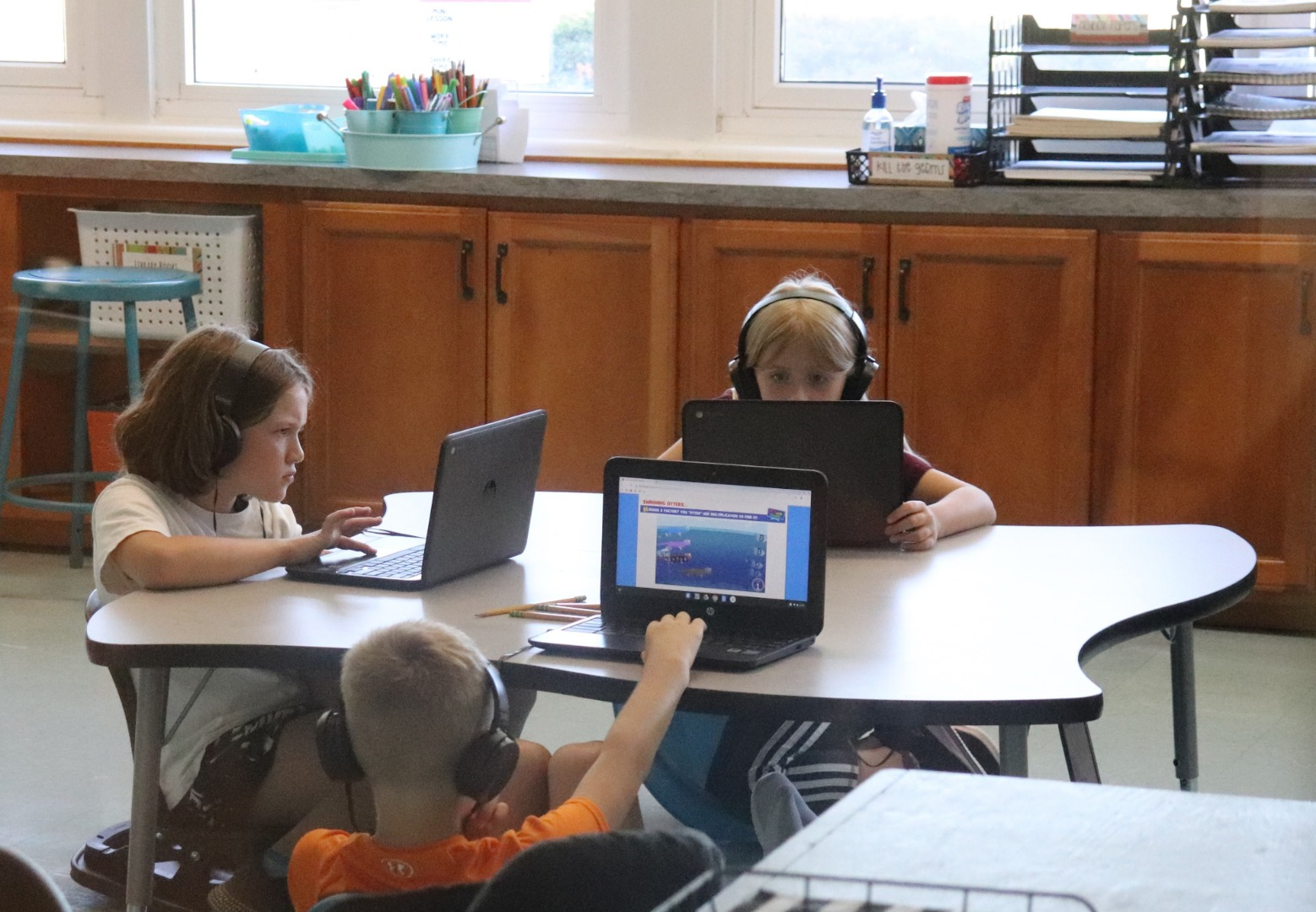 Three students working with individual laptops