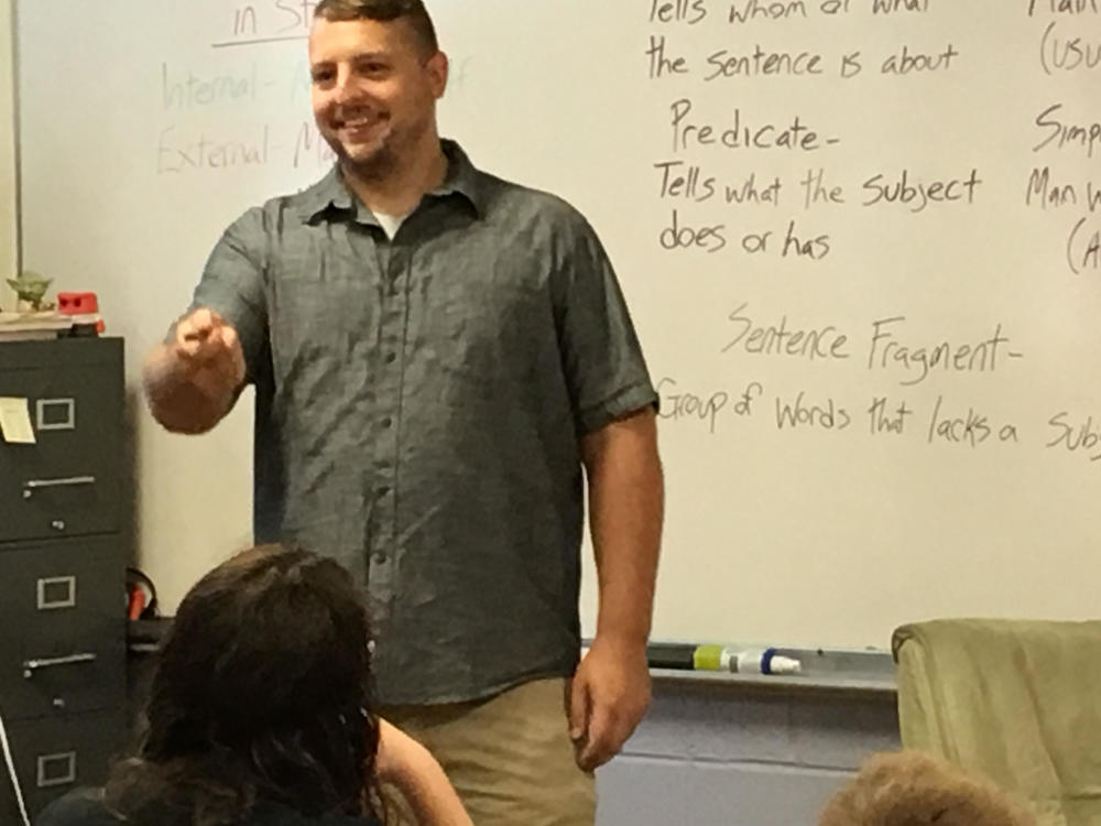 Teacher smiling and pointing