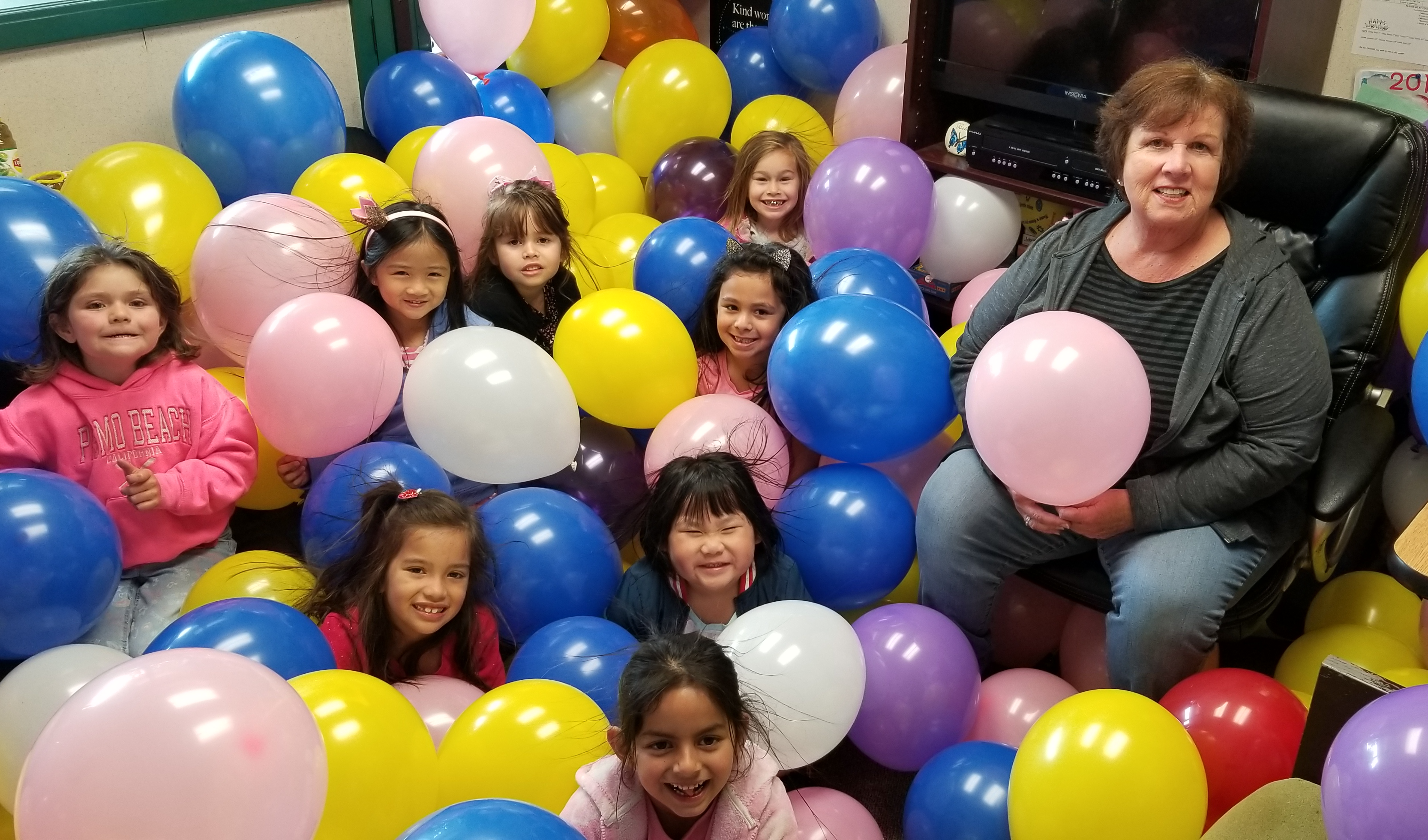 Counselor and  students surrounded by balloons.