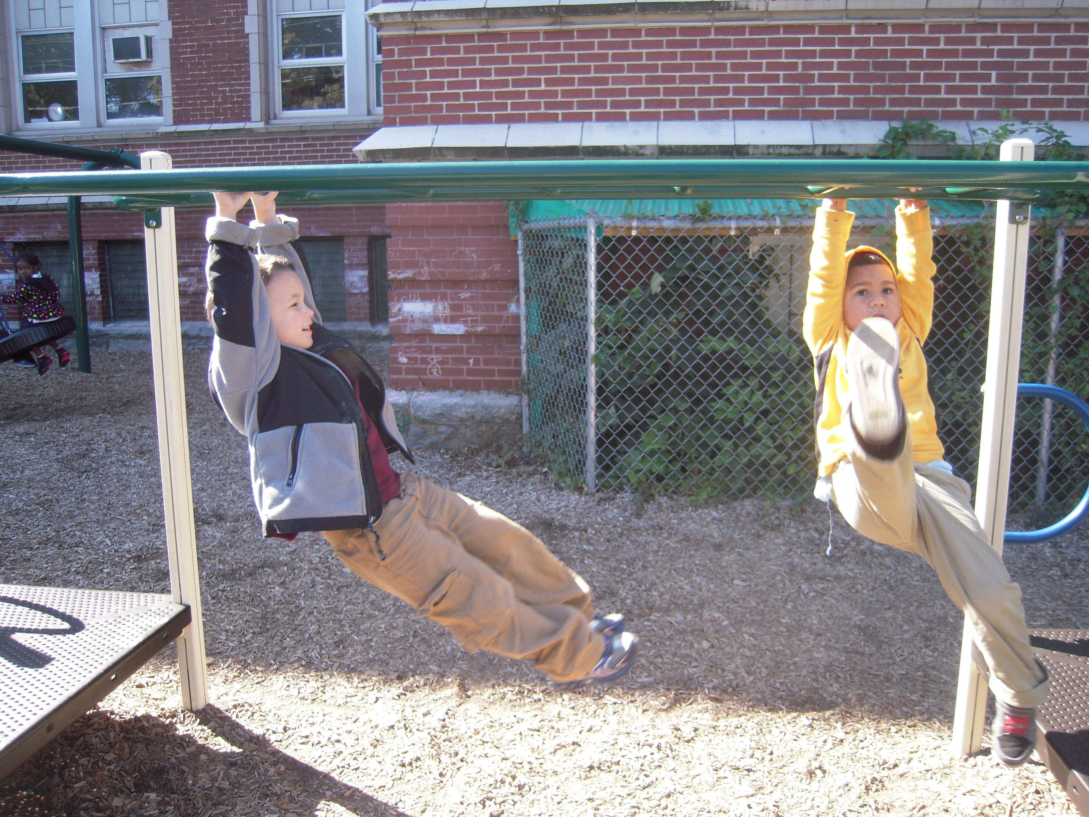 Two young students on playground equipment together