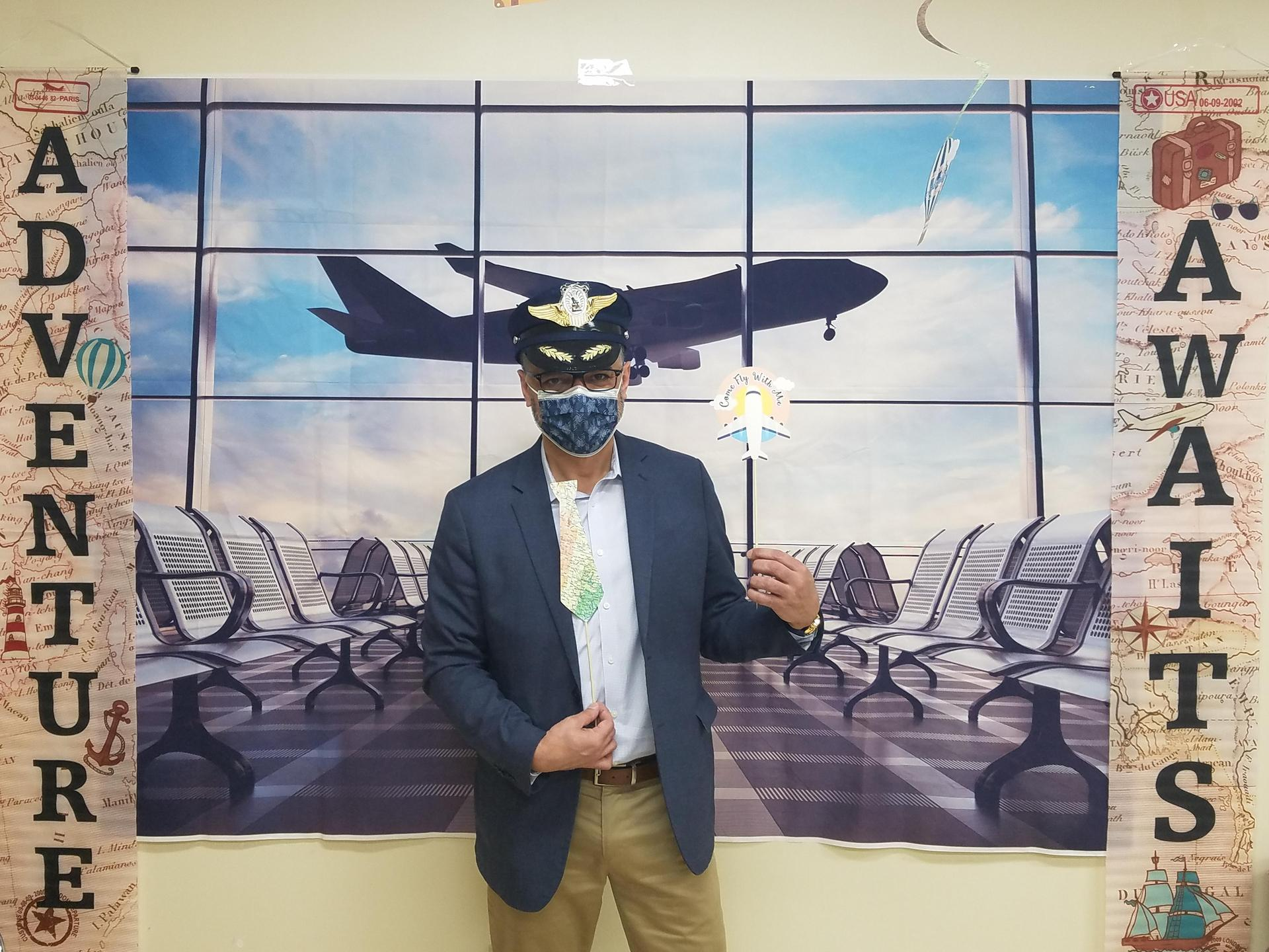 Man dressed as a piolet standing in front of an airport poster
