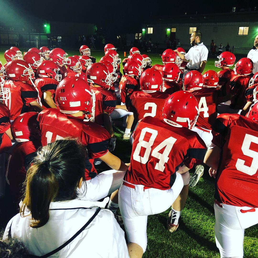 Football team huddling on knees by coach