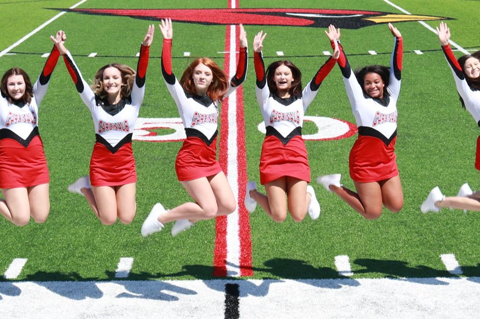 dance team jumping on football field