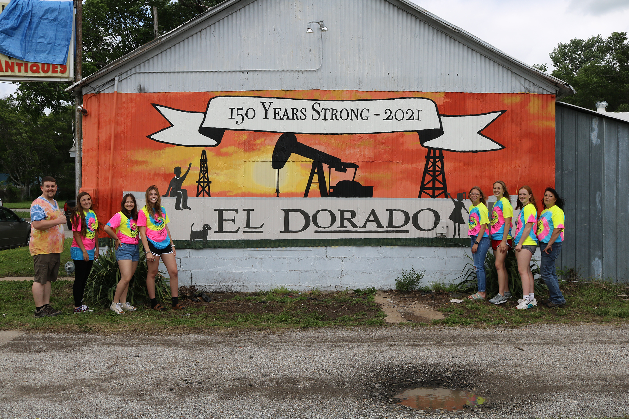 """Art students and teachers standing on either side of a mural that has an oil pump, oil derrick and the City of El Dorado sign with a banner that says """"150 Years Strong - 2021"""" across the top"""