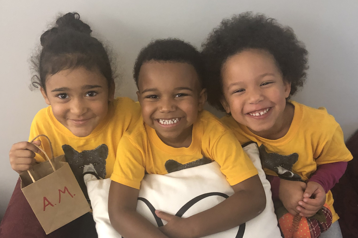 Three children in yellow t-shirts smiling at the camera