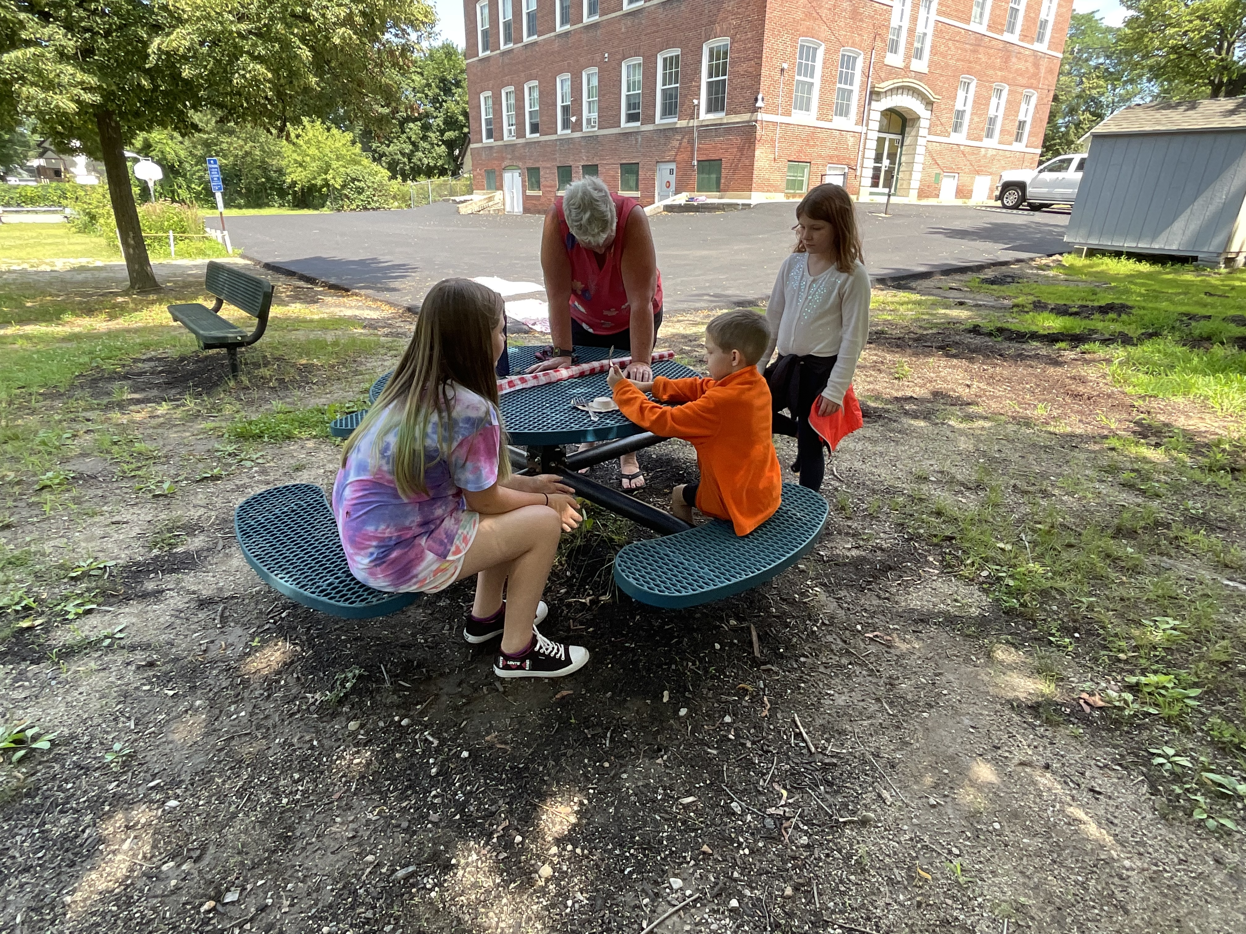 Students and a teacher exploring fossils outside at a table