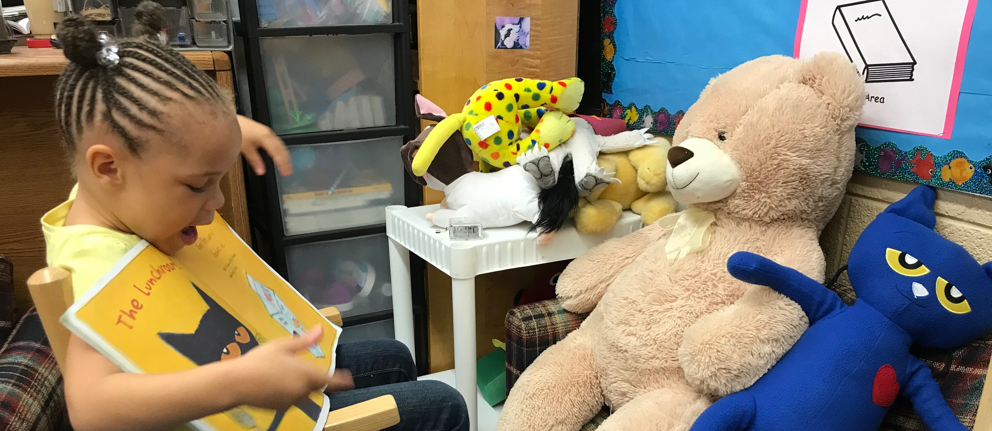 Johnson student reading to a teddy bear and Pete the Cat