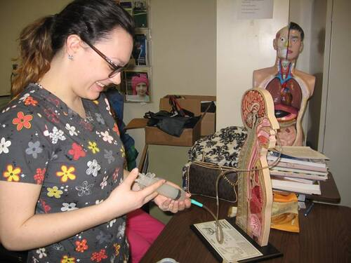Photos of the Nursing Assisting 2016 Program, a student learning anatomy