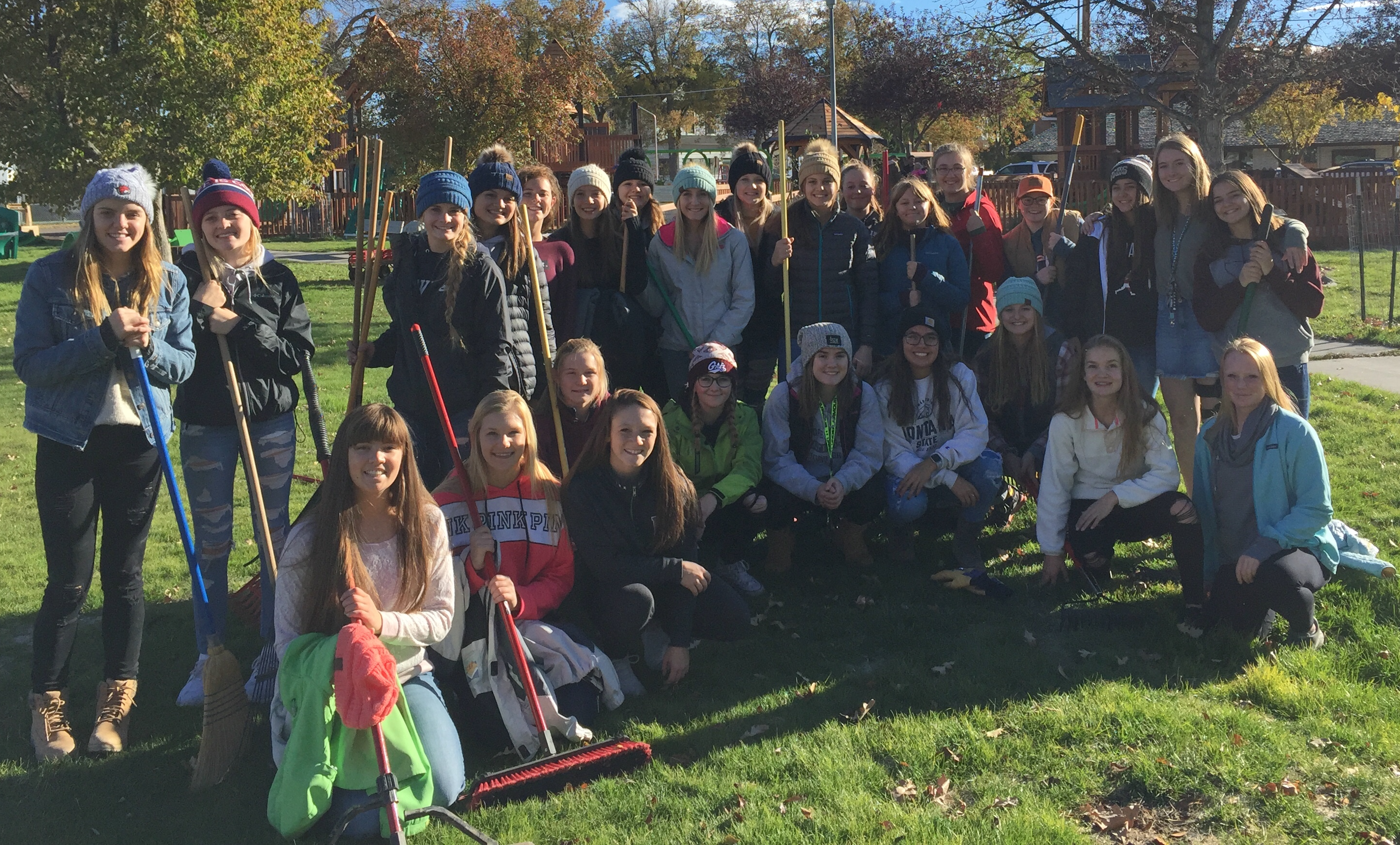 A photo of the volleyball team raking leaves at the Jaycee Park in October 2018