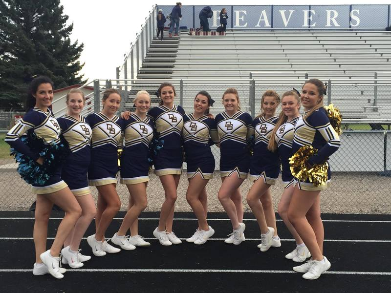 A photo of the Varsity Cheerleading team in their cheer uniforms at a stadium