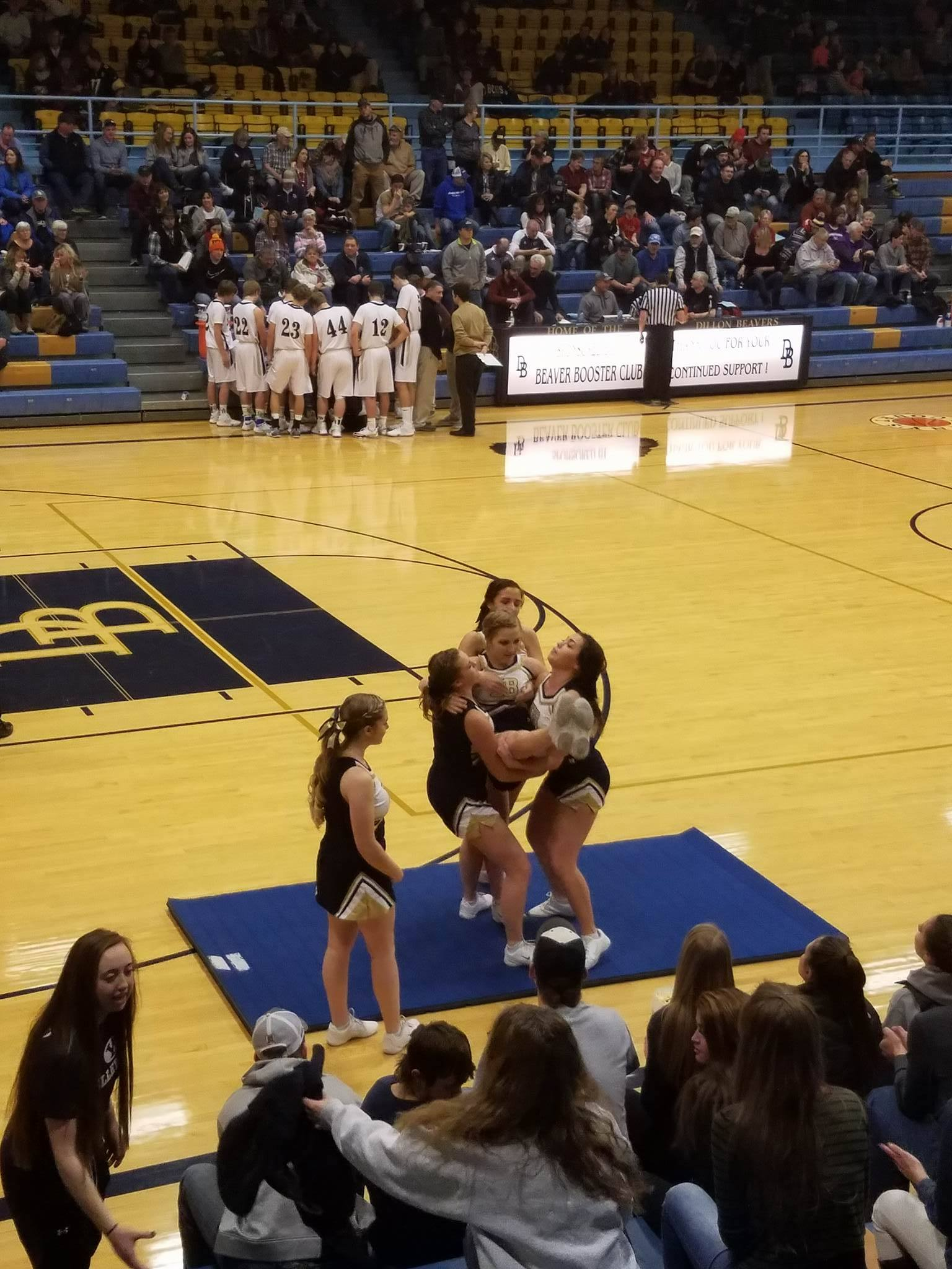 A photo of the cheerleaders finishing a stunt in a gym at a basketball game