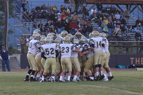 A photo of the football team in a huddle on the football field at a game