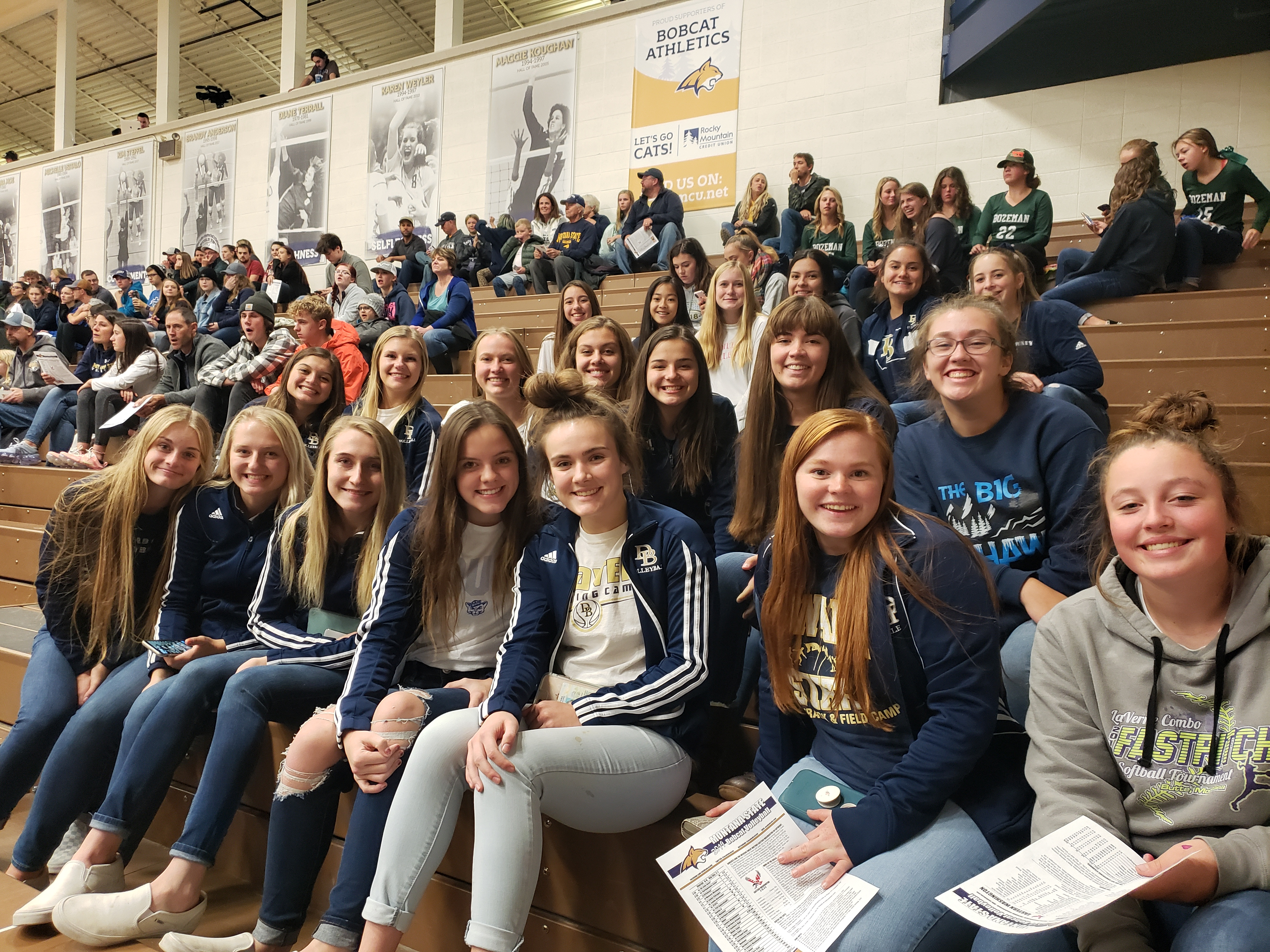 A photo of the volleyball team sitting in the stands enjoying watching some college volleyball