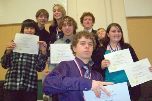 A photo of students holding awards and wearing medals