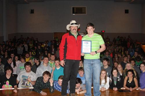"A photo of a student standing on a stage receiving the ""Doer of Good Deeds Award"" form the White Hat Coalition for their fundraising efforts"