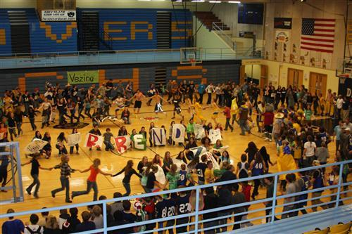A photo of students playing a game at a pep rally in the gym