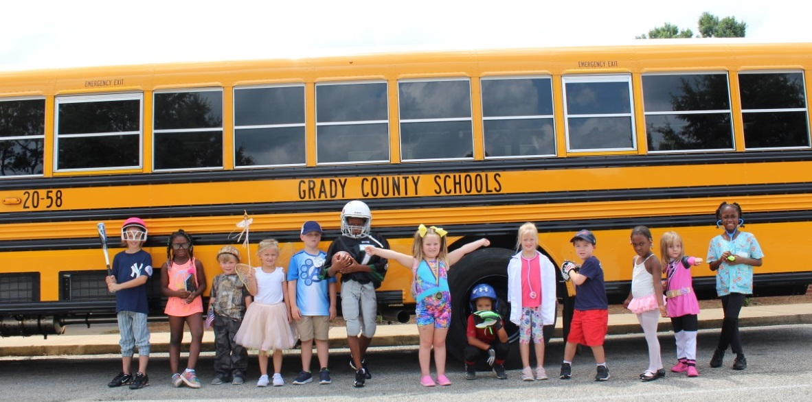 GCS students in costume in front of a bus
