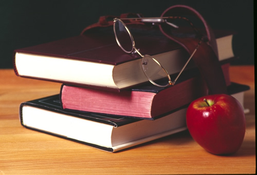 In the picture is a stack of three books, glasses and an apple.