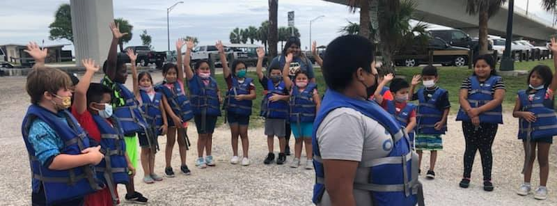 """A picture of Warfield Elementary students raising their hands to answer the question, """"Who has never been on a boat before?"""""""
