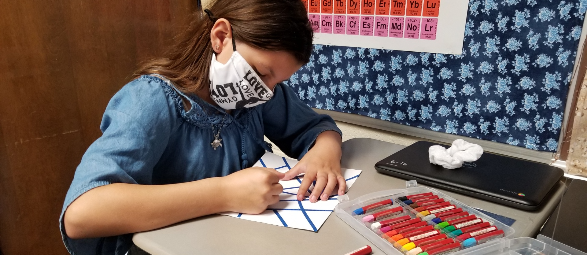 Student creating artwork with blue lines