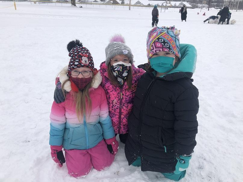Three girls kneeling in the snow wearing winter hats, coats and masks