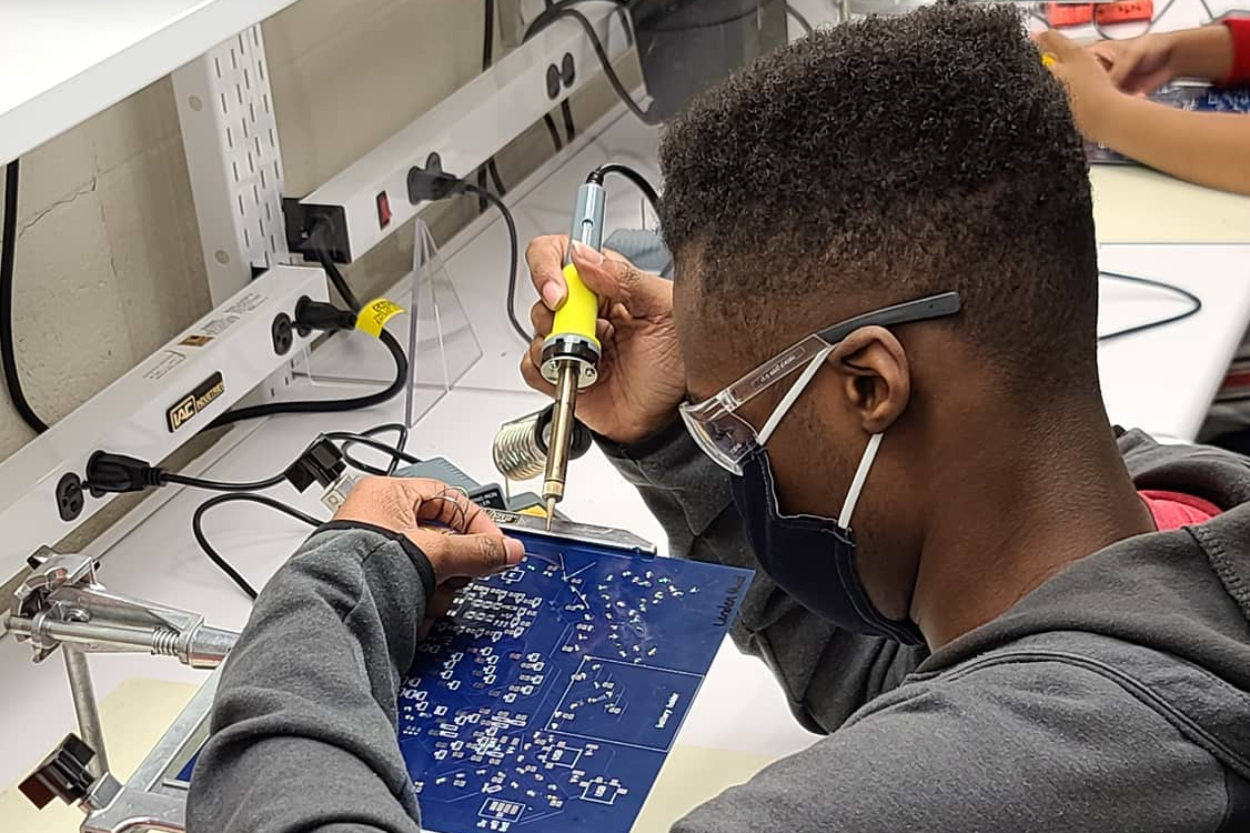 Student works on piece of computer equipment
