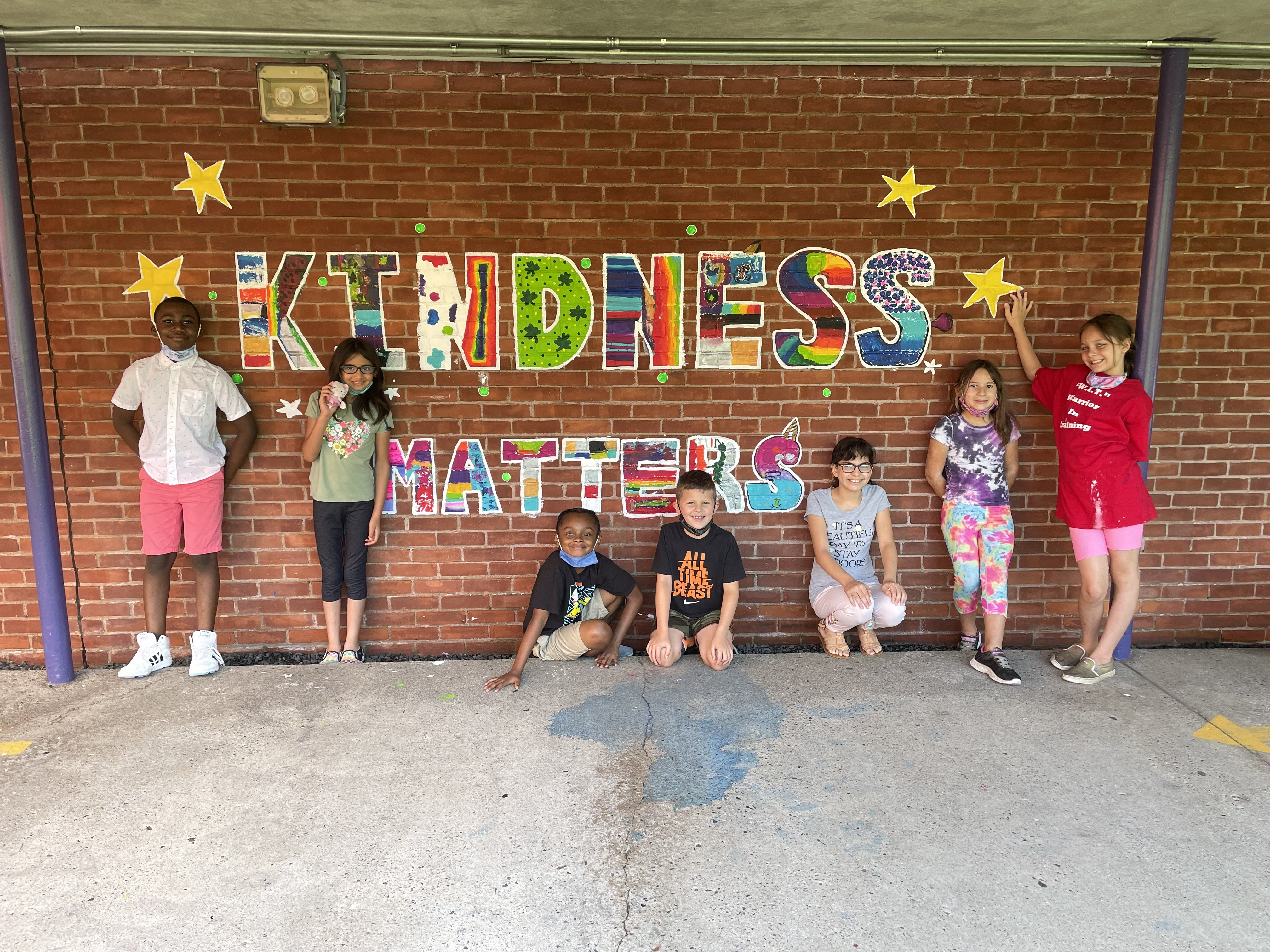 Students pose in front of the mural they created called Kindess Matters