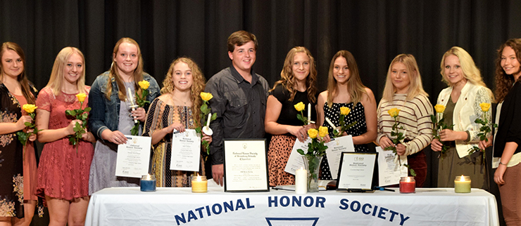 National honor society group photo with all students gathered around table holding flowers and rewards