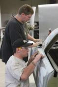 Students working on fixing a car