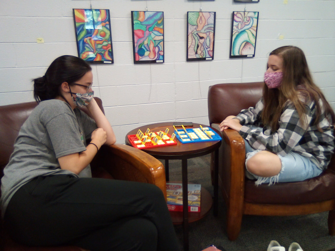 Students enjoying the library, reading books or playing board games