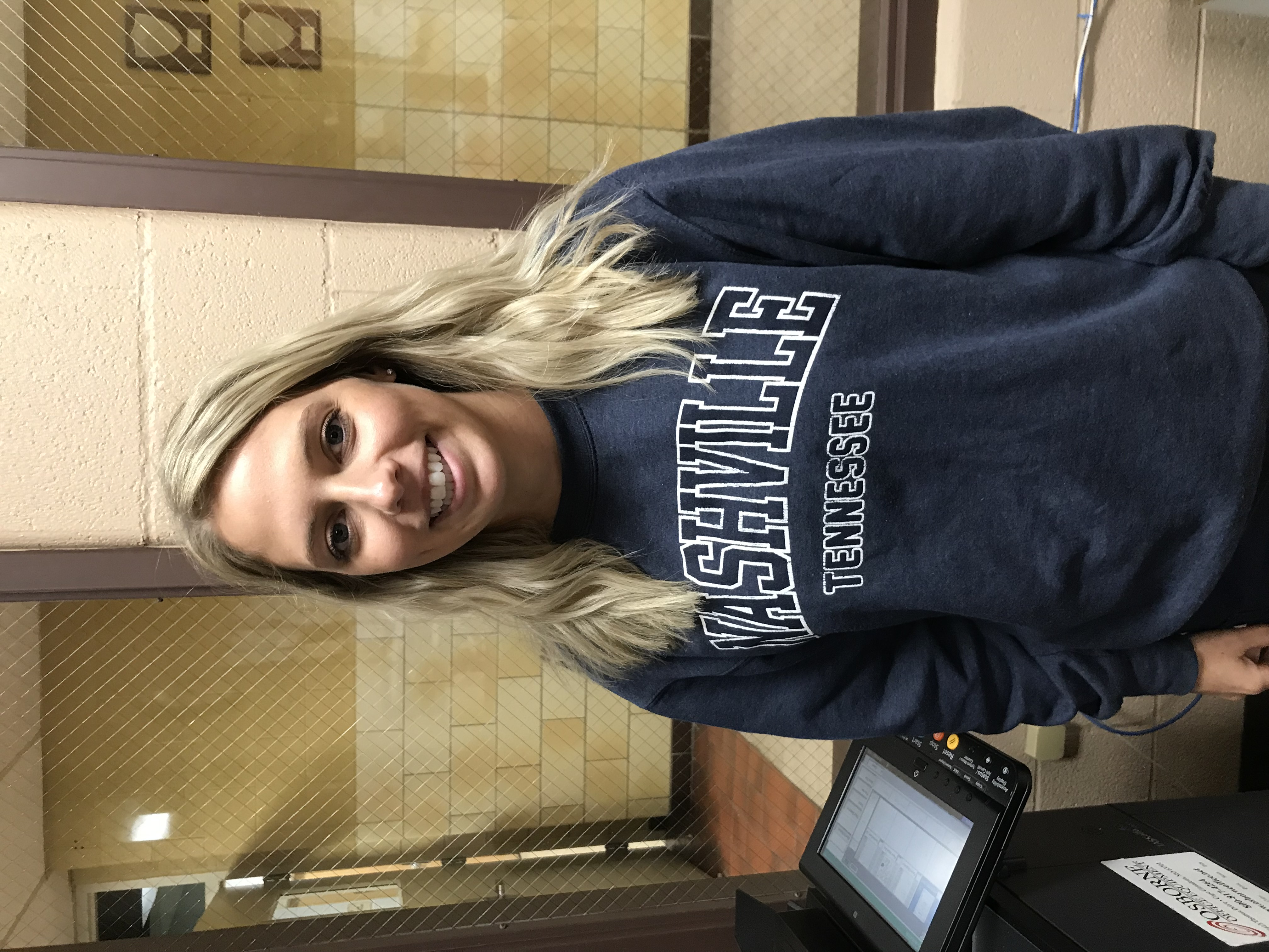 smiling woman with blonde hair and a navy blue sweatshirt