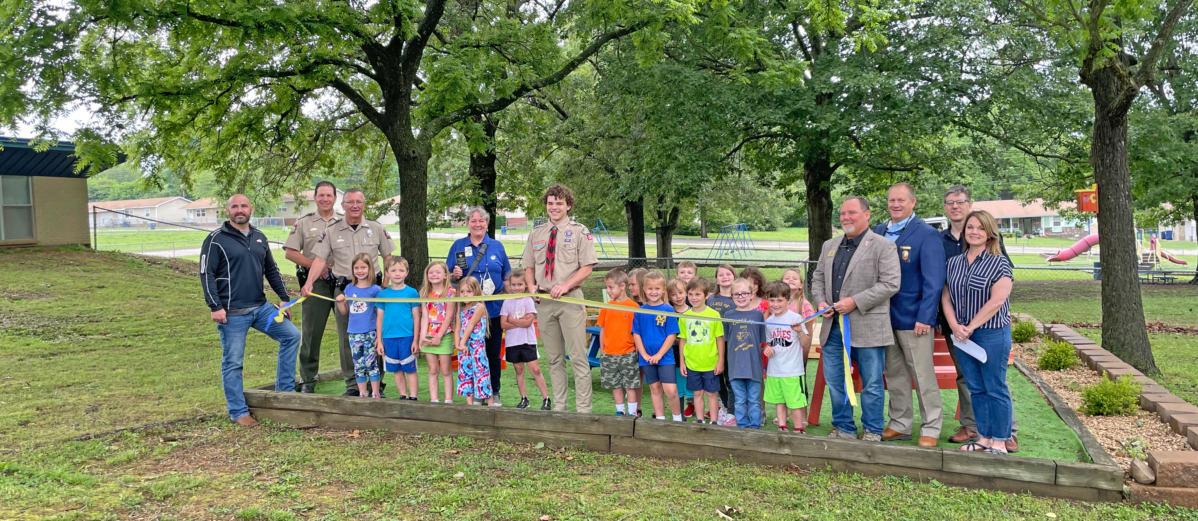 boy scout poses with students near outdoor classroom at MHK.