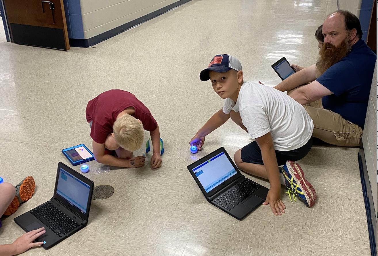 kids sitting in floor using laptops and mini-robots