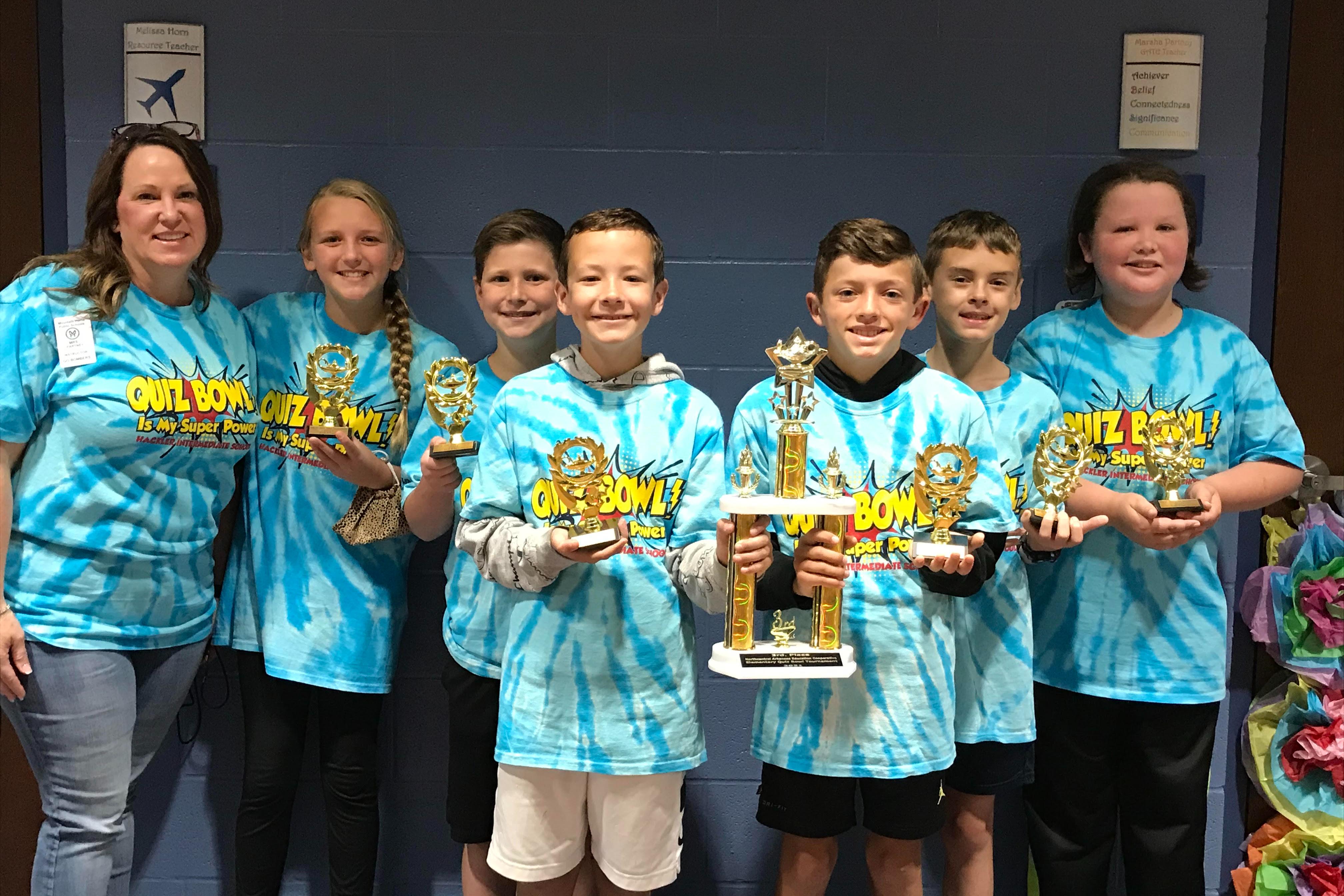 Quiz bowl team from intermediate school holding trophies.