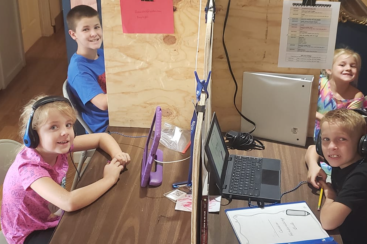 four children sit at homemade dividers working on digital devices