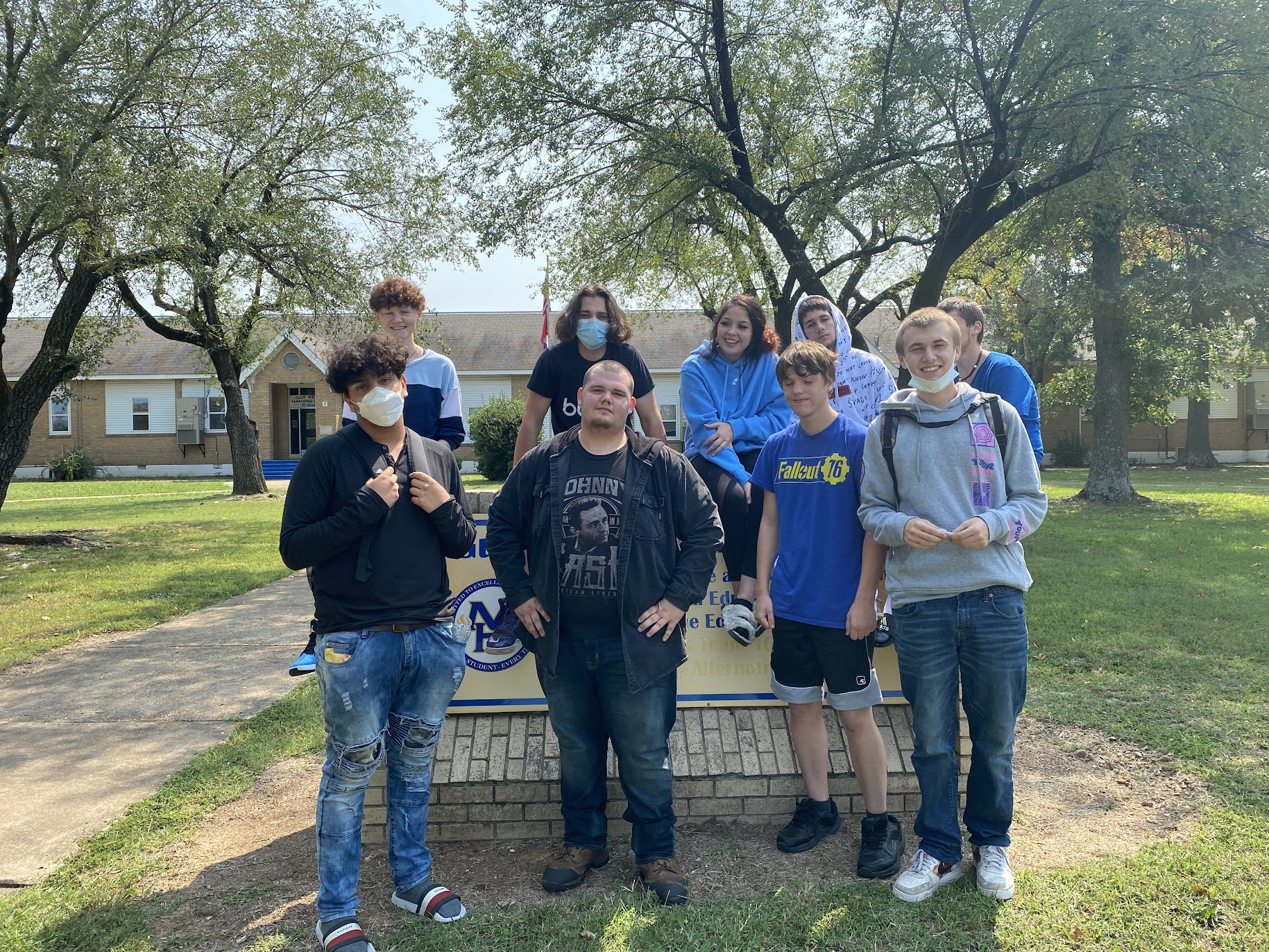 Group of students pose in front of school wearing their Bomber blue outfits
