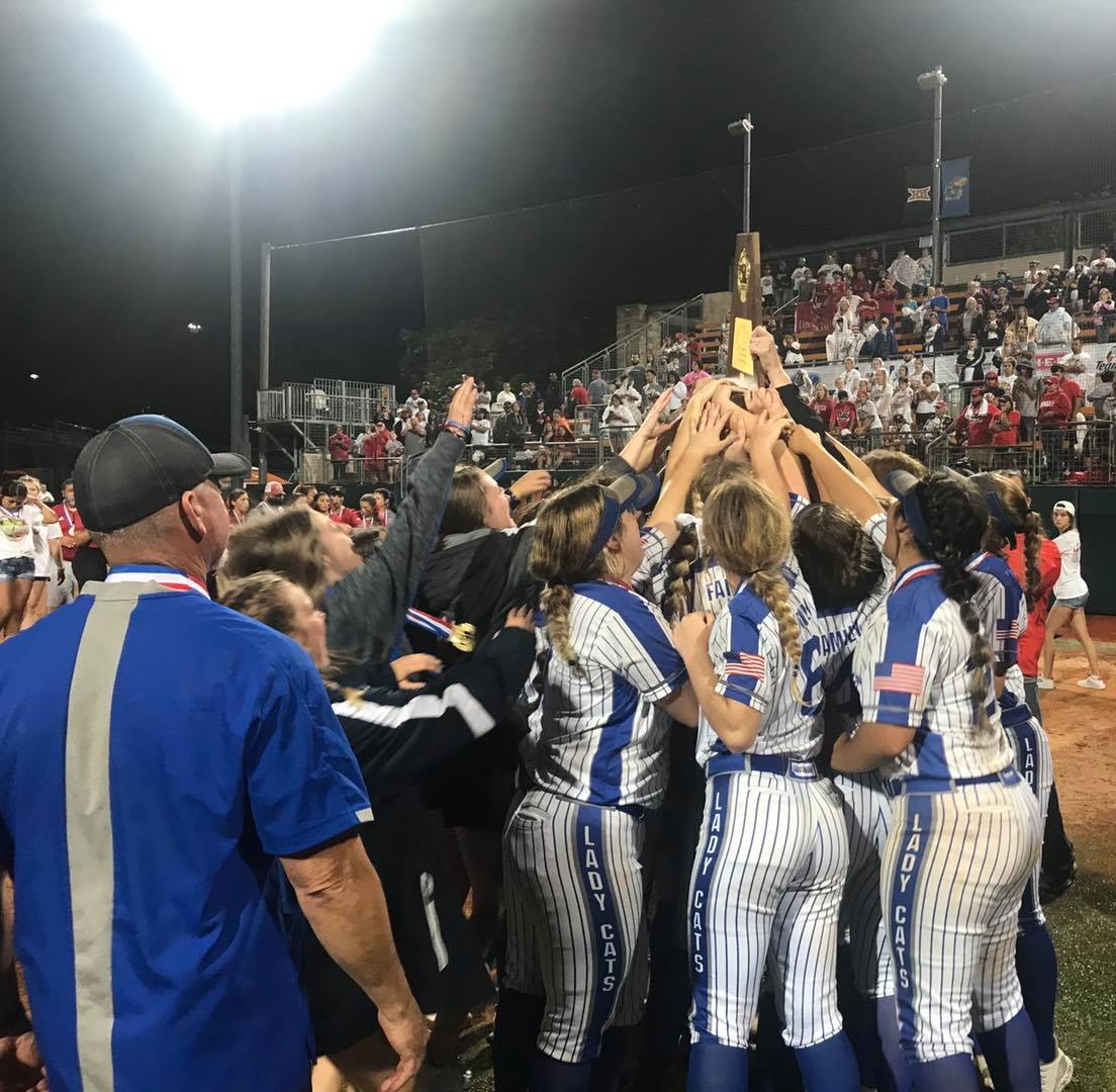 Lady Cat softball state champions touching trophy as a group
