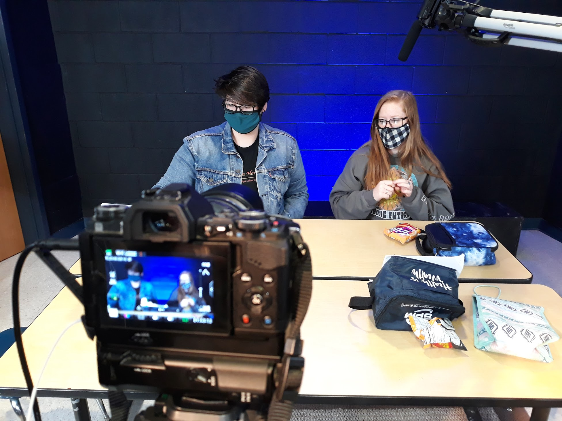 Students sitting in front of a camera with masks on