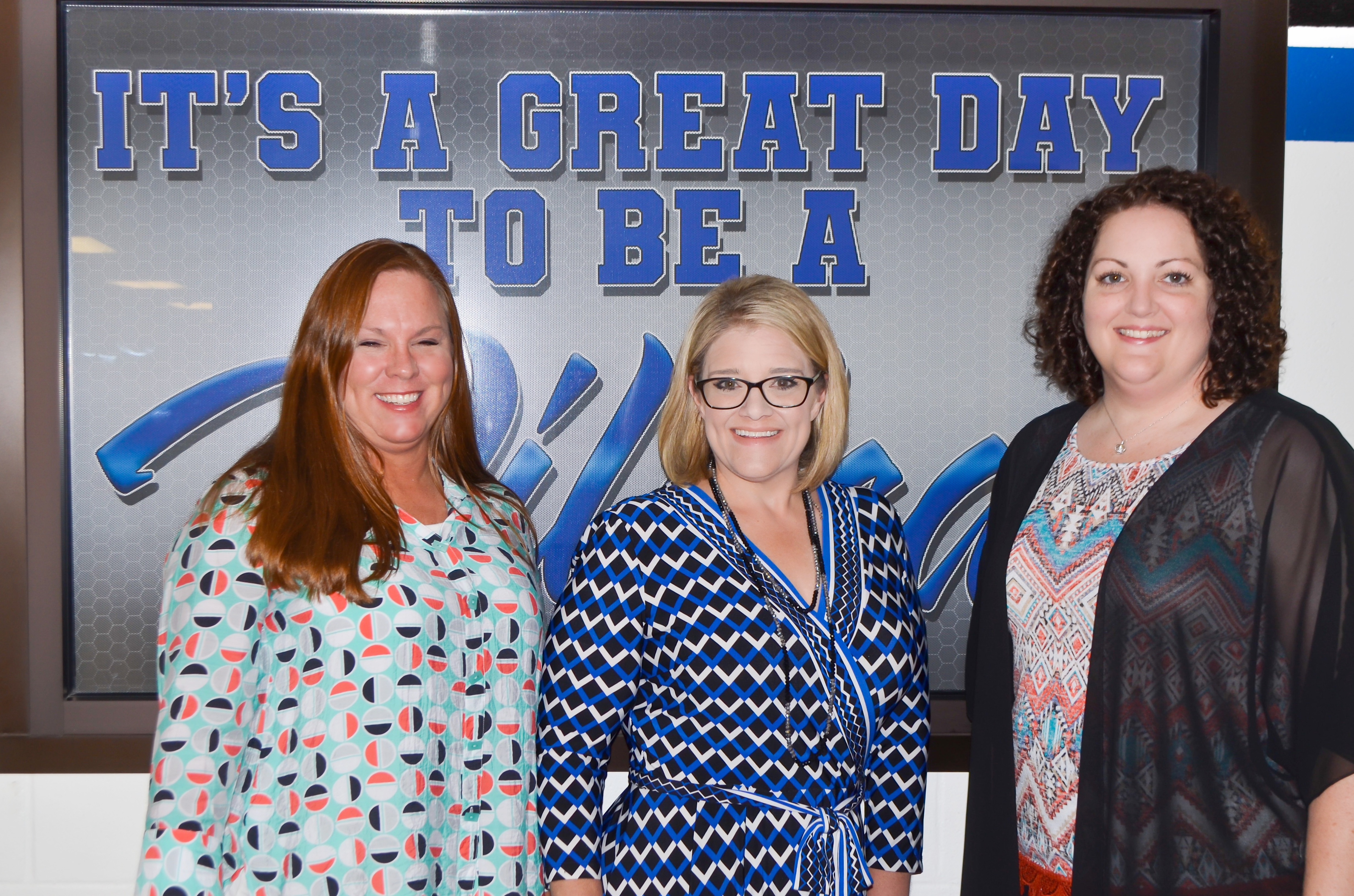"""Mrs. Knight, Mrs. Melton, and Mrs. Timmons posing in front of the """"it's a great day to be a wildcat"""" window."""