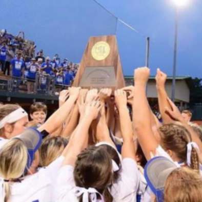 lady cat softball players holding the state trophy raised over a huddle