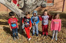 kids standing next to a tree