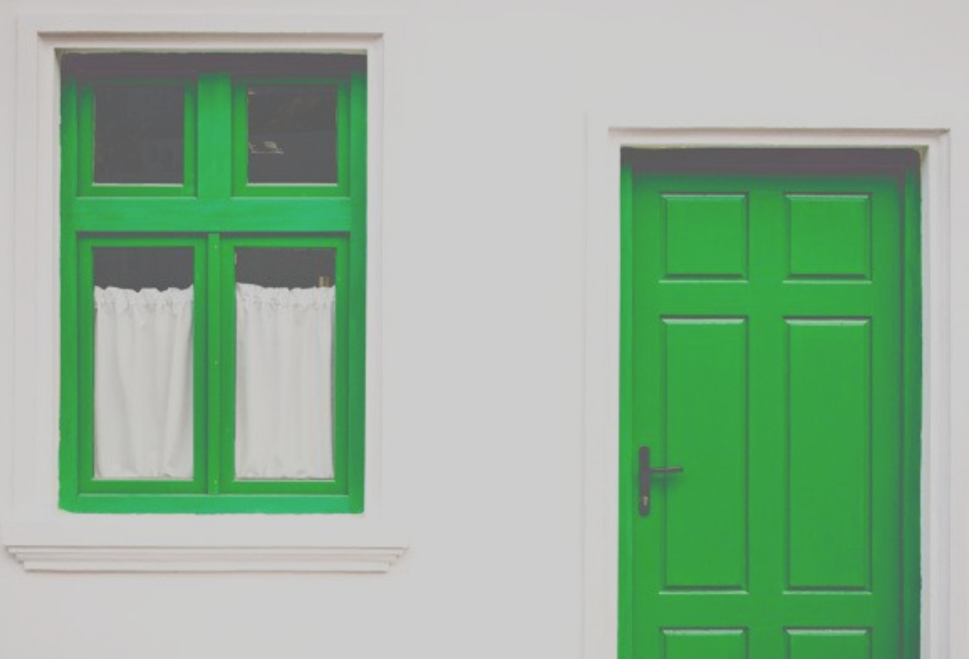 A photo of a house with green door and window